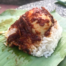 Nasi Lemak (Medan Selera Mutiara, Penang): coconut rice with sambal, anchovies & egg, wrapped in a banana leaf